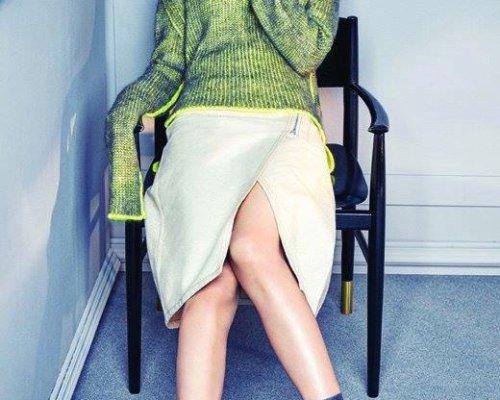 Beiger asymmetrisch geschnittener Rock, grüner Rollkragen-Pullover und schwarze Ankle Boots aus Leder von Acne Studios.