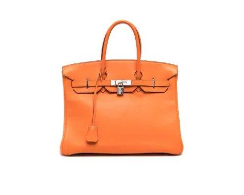 Beiger Trenchcoat, Jeans, braune Boots und die orangene Hermés Birkin Bag Handtasche