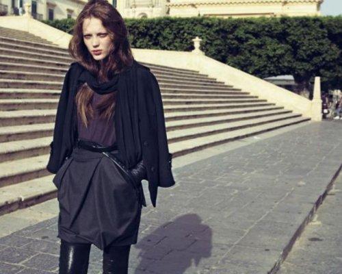 Overknee-Stiefel aus schwarzem Leder, schwarzer Ballonrock mit dünnem Ledergürtel, Baumwoll-Top in dunkellila und schwarzer Cardigan.