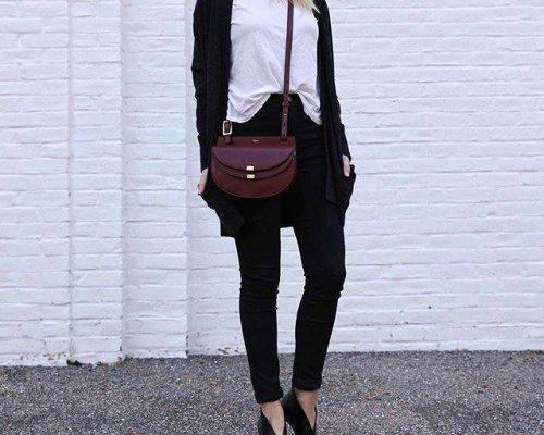 Schwarze 7/8-Hose, schwarzer Longcardigan, weißes Shirt und dunkelrote Crossoverbag des Luxuslabels Derek Lam.