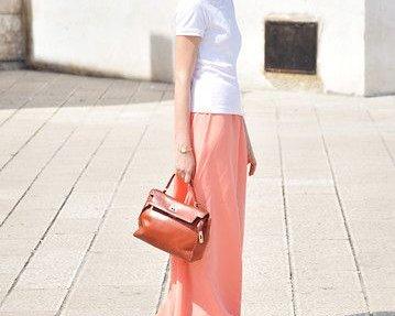 Weißes T-Shirt,  pfirsichfarbener Maxirock aus Seide und perfekt dazu eine Henkeltasche aus braunem Leder.