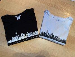 2 T-Shirts mit selben Motiv in unterschiedlichen Farben.