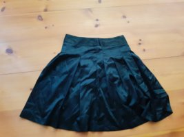 Glänzender schwarzer Faltenrock