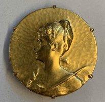 Goldbrosche mit Frauenmotiv