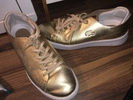 Goldene Lacoste Schuhe