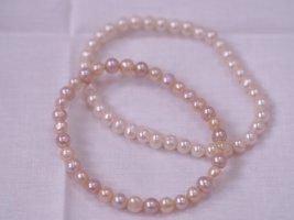 Jeweils ein Perlenarmband, weiß oder rosa