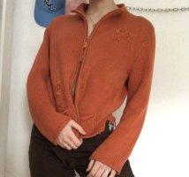 orangene strickjacke mit blumen