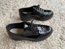 Schwarze Schnürschuhe mit Lochmuster und dicker Sohle
