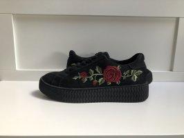 schwarze Sneaker mit Plateausohle und Blumenmuster
