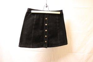 schwarzer Lederrock mit messingfarbener Knopfleiste