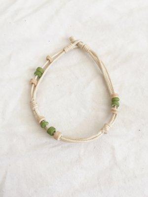 Armband aus beigem Stoff mit grünen Perlen