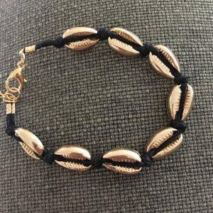 Armband mit goldfarbenen Anhängern in Muschel Form