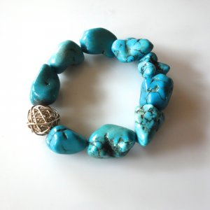 Armband mit türkisen Halbedelsteinen (türkise Howlithe), Indien, 2 cm Länge, mit silberfarbigem Zwischenteil (durchbrochene Kugel), auf Gummi gefädelt, bester Zustand