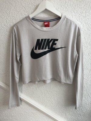 Beigenes, langärmeliges Nike Cropped Oberteil mit auffälligem Logo