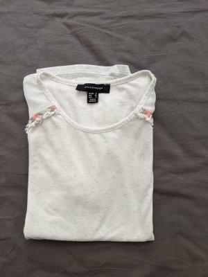 beiges T-Shirt mit bunter Applikation an den Schultern