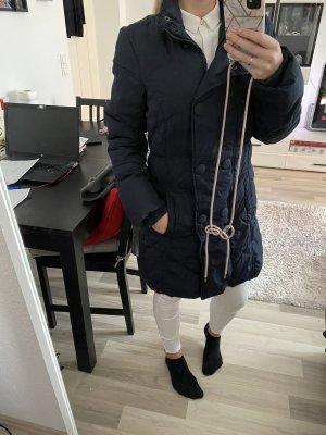 Blaue Jacke mit dicken Knöpfen und Reißverschluss
