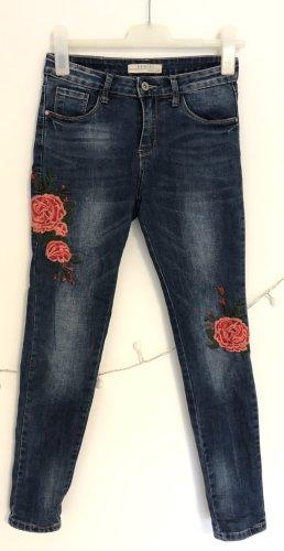 Blaue Jeanshose mit Blumenbesatz