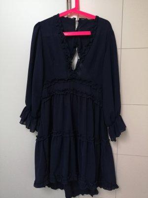 Dunkelblaues Kleid mit tiefem Ausschnitt und offenem Rücken.