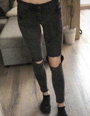 Dunkle Jeans mit Löchern