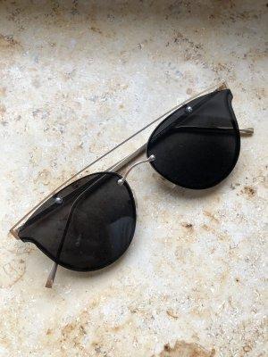 Dunkle Sonnenbrille mit goldenem Bügel