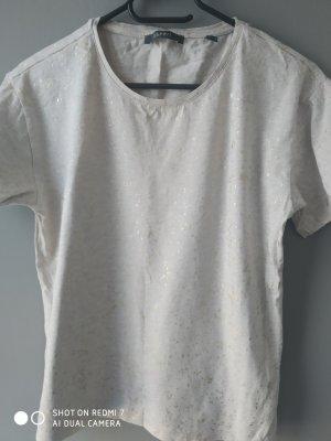 Ein beige T-Shirt mit Goldfleckchen