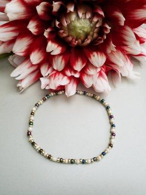 Filigranes Armband mit cremefarbenen, dunklen und goldfarbenen Perlen