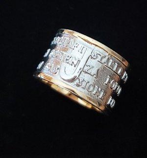 gold- silberfarbener Ring mit der Inschrift Mut, Stärke, Leidenschaft