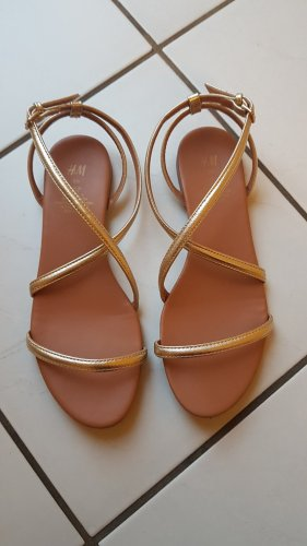 Goldene Sandalen mit Kreuzschnürung