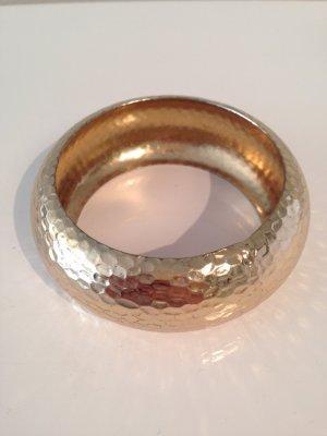 Goldener Armreif aus gehämmerten Metall
