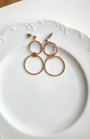 goldfarbene Ohrringe mit aneinander hängenden Kreisen