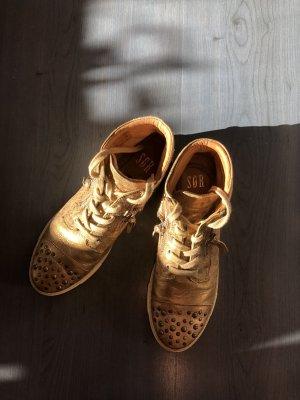 Goldfarbene Sneaker mit Nieten