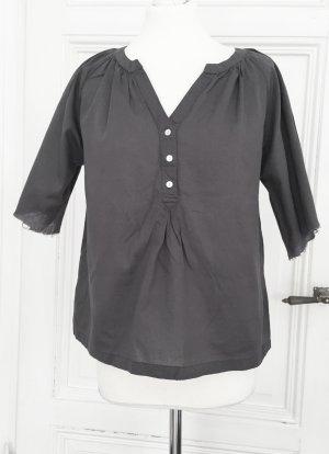 Graue Bluse mit breiten ausgefransten Ärmeln.