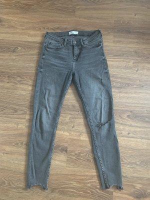 Graue Jeans mit Löchern