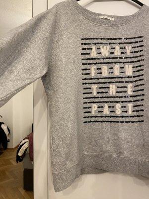 Grauer Pullover mit Schriftzug und Pailetten