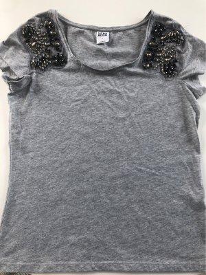Graues Shirt mit Applikationen auf der Ärmeln