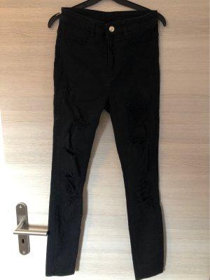 Jeanshose schwarz mit Löchern an beiden Beinen