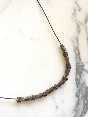 Kette aus schwarzem Lederband mit bronzefarbenen Details