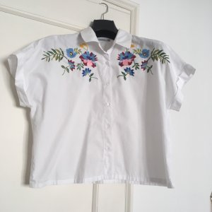 Kurze kastige weiße Bluse mit Blumenstickerei.