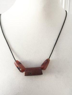 Lange Kette aus dunkelbraunem Echtlederband und roten Steinen