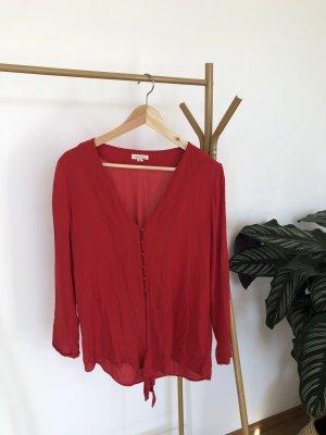 Lockere rote Bluse zum Binden