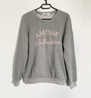 Pullover in Grau mit rosafarbener Aufschrift
