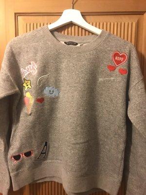 Pullover mit verschiedenen Stickern drauf