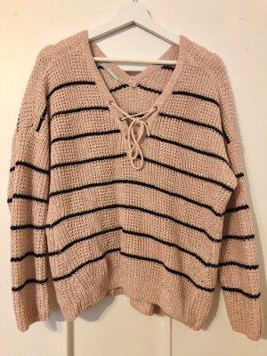 Rosa Farbener Pullover mit schwarzen Streifen und Schnürung am Ausschnitt