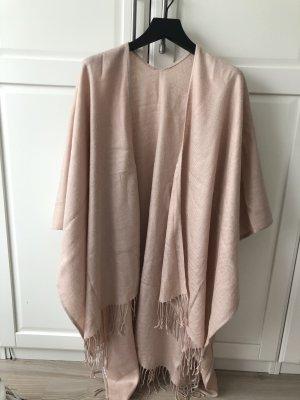 Poncho en tricot or rose