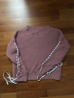 Rosa Strickpullover mit weißen Bändern/ Schleifen