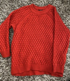 Roter Pullover mit Zopfmuster