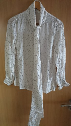 Schöne weiße Bluse mit goldenen Punkten und einer Schleife
