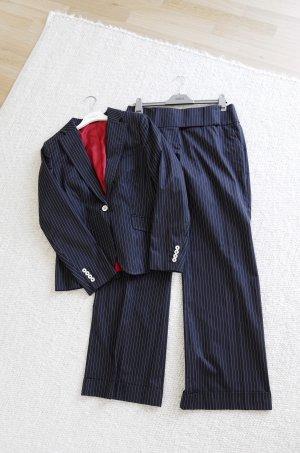 Schwarz weiß gestreifter Anzug mit roten Details