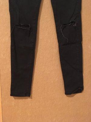 Schwarze enge Hose mit Einschnitten im Knie