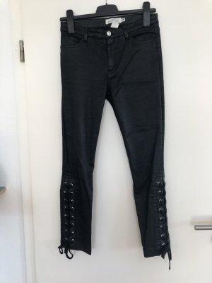 schwarze gewachste Hose mit seitlicher Schürfung